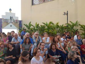 Turisti seguono un evento nella Casa degli Artisti